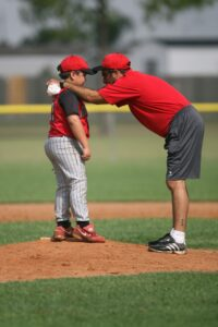 Coach talking to young pitcher on the mound during pitcher lessons