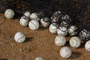 baseballs next to net after pitching lessons for off season