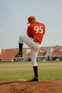baseball pitcher with knee up using pitching velocity to strike out hitters
